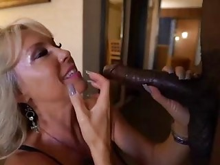 Slutty, mature blonde is giving a titjob to a black guy and having sex with him